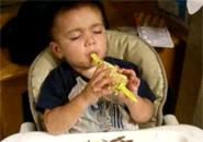 Cậu bé vừa ngủ vừa ăn ngô
